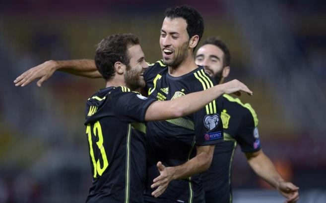 Juan Mata celebra con Busquets su gol en Skopje
