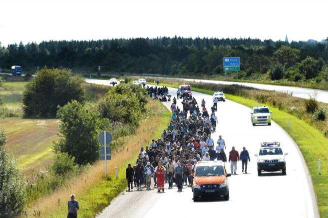 Una gran columna de refugiados caminan por una autovía de Suecia.