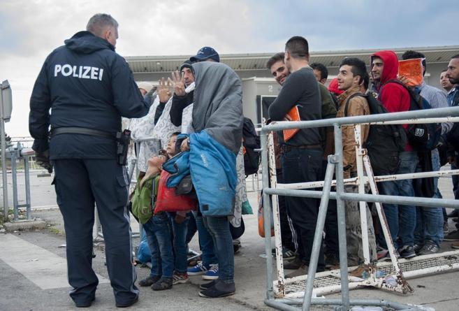 Migrantes procedentes de Hungría esperan un bus en la frontera con...