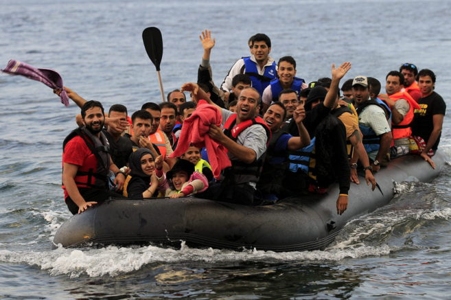 Varios refugiados sirios llegan en una lancha neumática a la costa de...