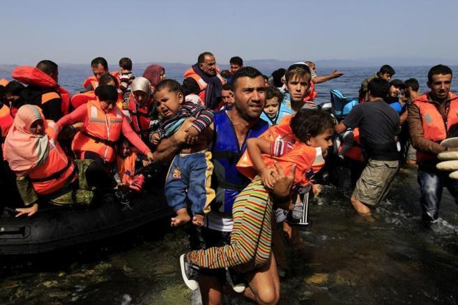 Un hombre desembarca con dos niños en brazos de una de las lanchas de...
