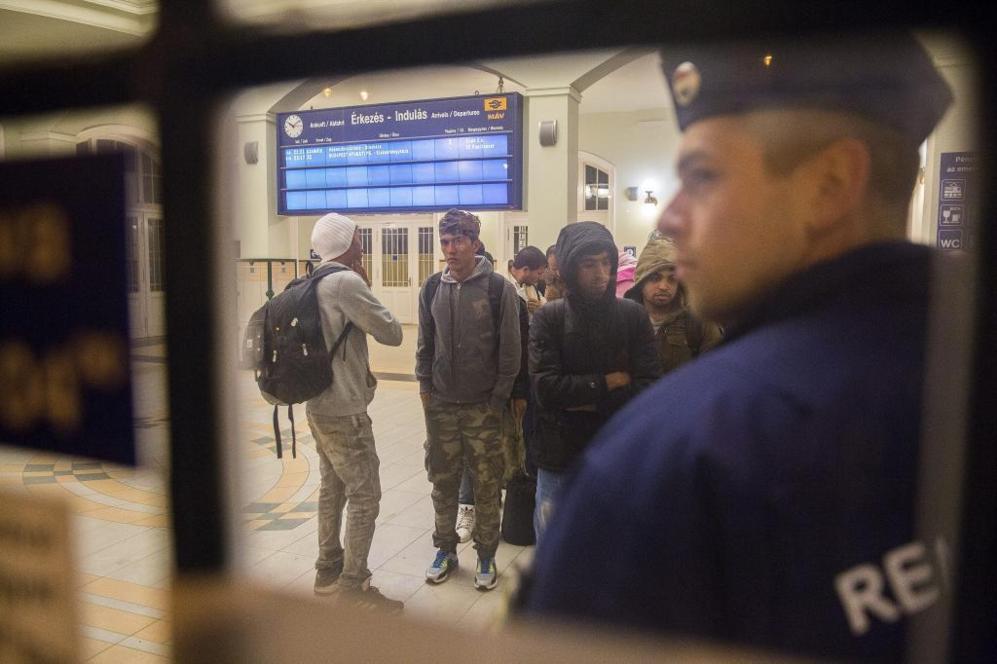 Policías húngaros detienen a refugiados en la estación de tren de...