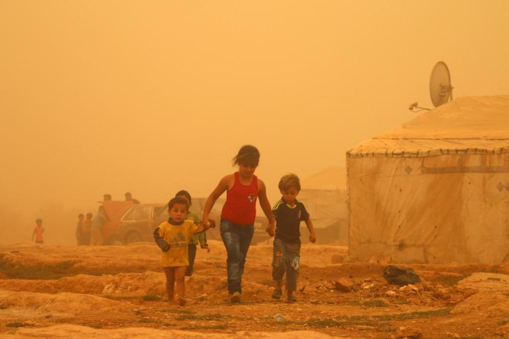 Cuatro niños sirios caminan durante una tormenta de arena en las...