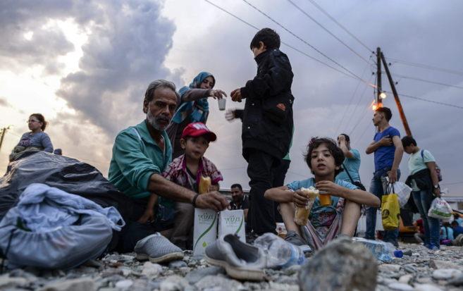 Inmigrantes hacen una parada para comer en Gevgelija (Macedonia).
