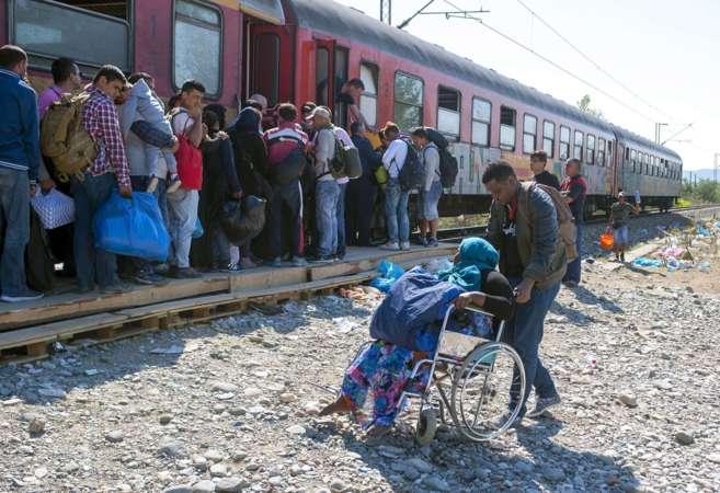 Refugiados hacen cola para entrar en un tren cerca de Gevgelija...