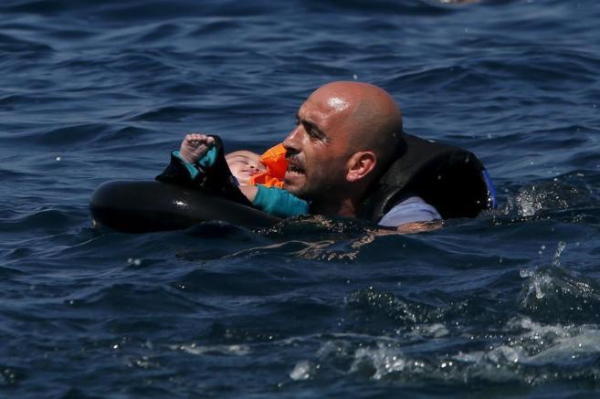 Un refugiado sirio sostiene a un bebé en un salvavidas en la isla de...