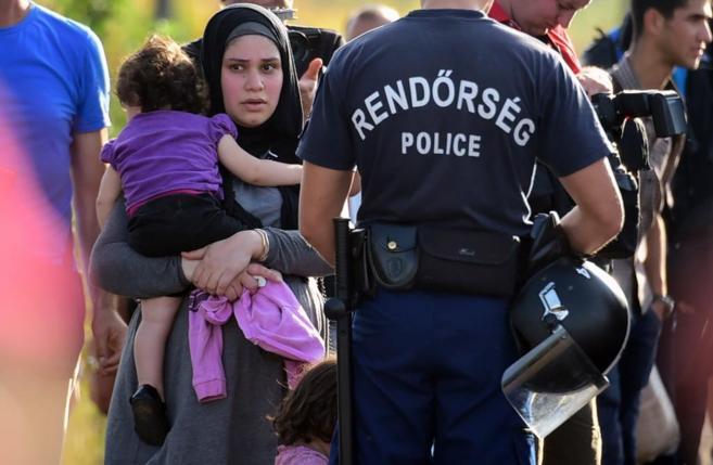Una refugiada observa cómo la policía impide el paso en la frontera,...