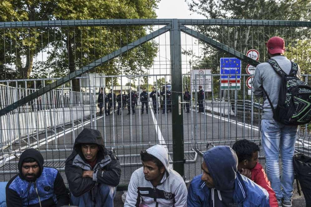 Varios refugiados esperan en el punto de entrada a Hungría desde...