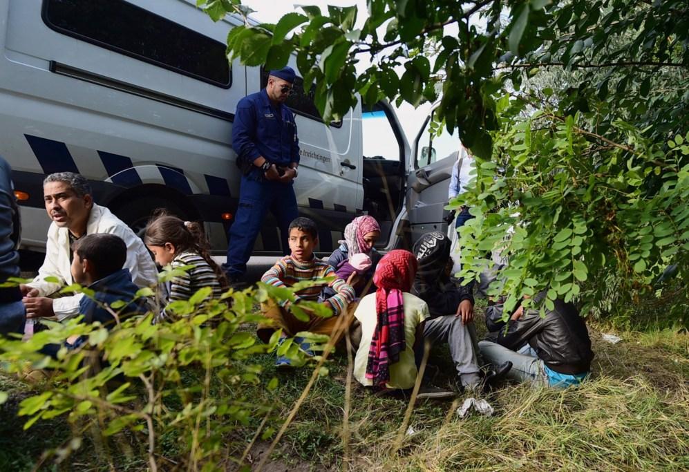 Varias familias con niños esperan junto a un furgón cerca de Roszke...