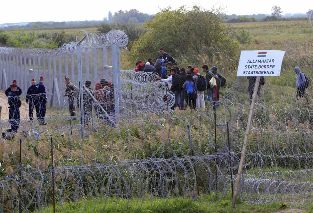 Un grupo de migrantes espera junto a la alambrada mientras varios...