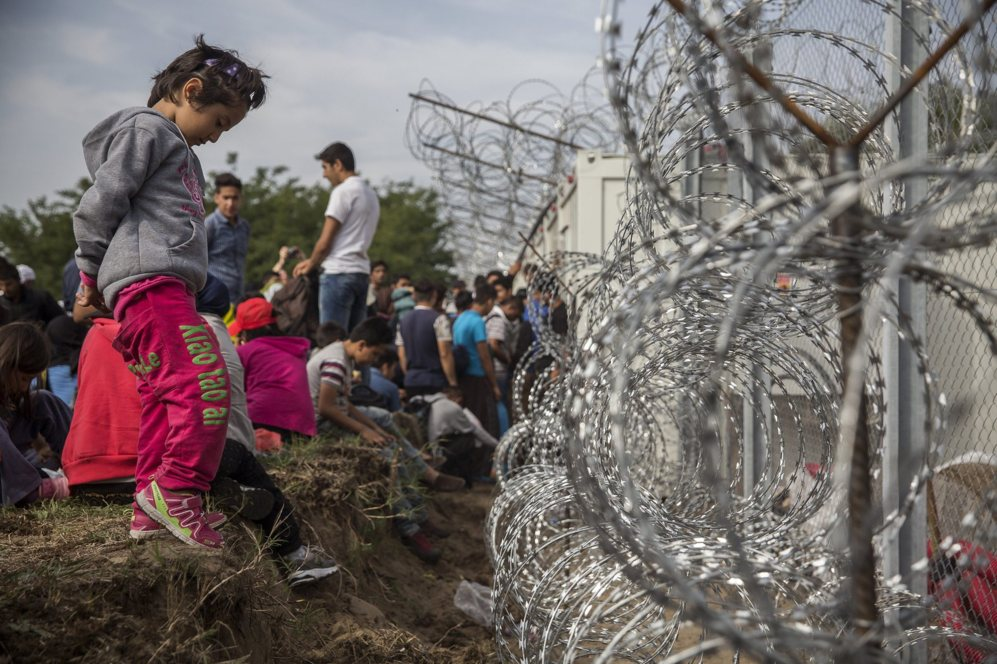 Varias familias esperan en el lado serbio de la valla, junto al punto...