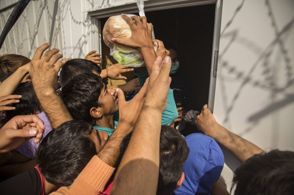 Decenas de personas reciben alimentos desde el punto de acceso para...