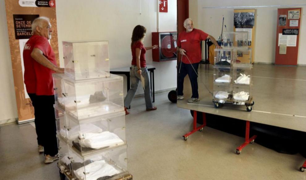 Un trabajador entrega varias urnas en un colegio electoral de...