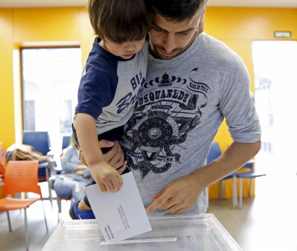 El futbolista Gerard Pique y su hijo Milan introducen un sobre en la...