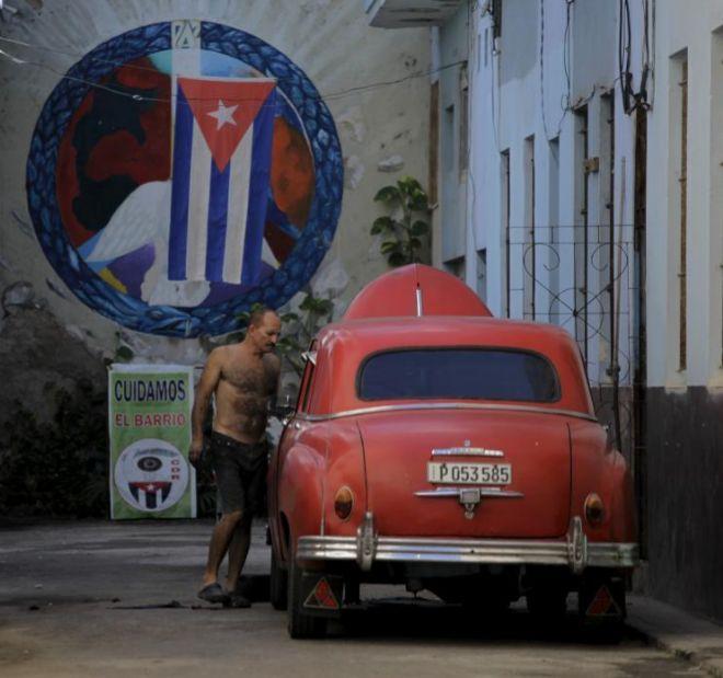 Un cubano repara un viejo coche fabricado antes de la Revolución, en...