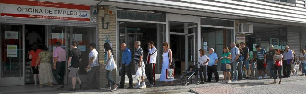 Personas guardan la cola de una oficina de empleo