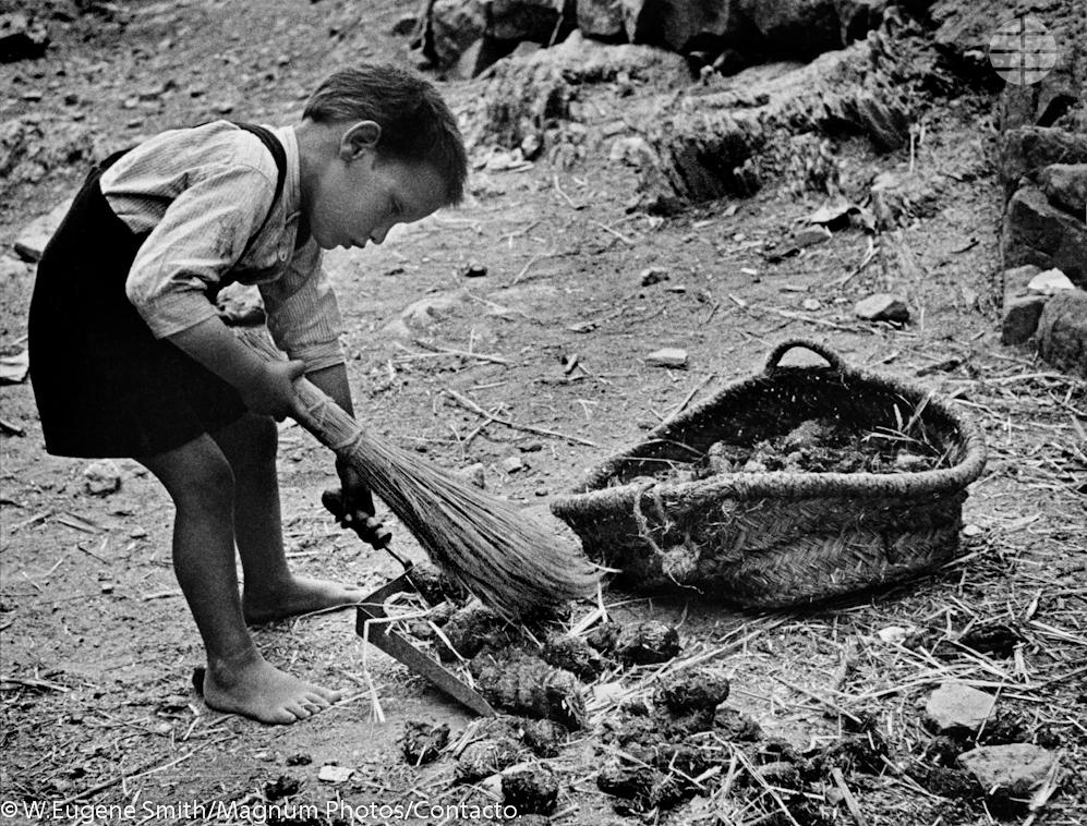 Niño trabando. Lutier, el hijo de 5 años de la familia Curiel, barre el estiércol frente a su casa. El estiércol se usará como fertilizante en los ocho campos que la familia posee o alquila a un par de millas del pueblo.