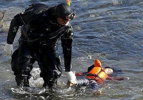 Un buzo griego saca del agua el cadáver de una niña en una playa de...