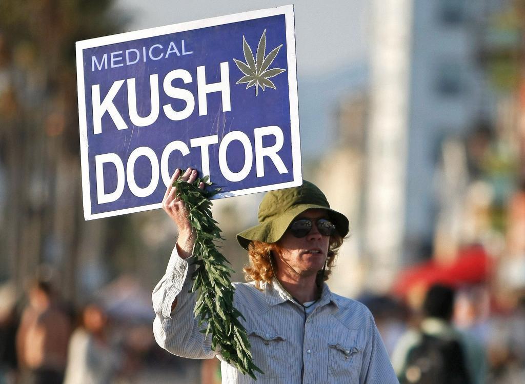 Un hombre porta un cartel de un dispensario de marihuana medicinal en Venice Beach, Los Angeles.