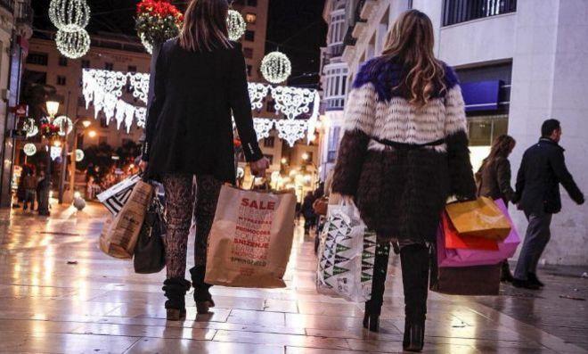 Dos chicas de compras en un centro comercial durante las pasadas...