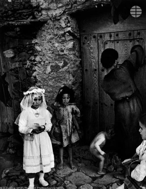 Vestida de primera comunión. Lorenza Curiel, de 7 años, espera a su madre en la puerta de su casa para ir a la iglesia.