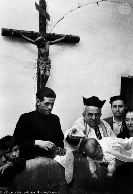 Un bautizo. Mientras que su padrino lo sostiene sobre una fuente, el sacerdote Don Manuel seca la cabeza del recién nacido, Buenaventura Jiménez Morena, después de su bautismo en la iglesia del pueblo.