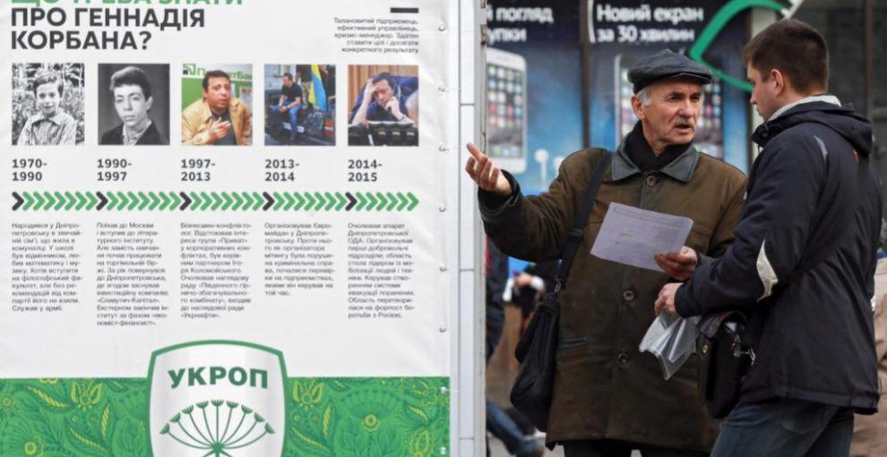 Dos hombres conversan junto al puesto electoral de 'Asociación de...