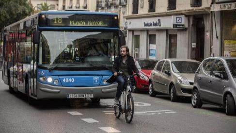 63d04478b2f Un ciclista pedalea frente a un autobús.