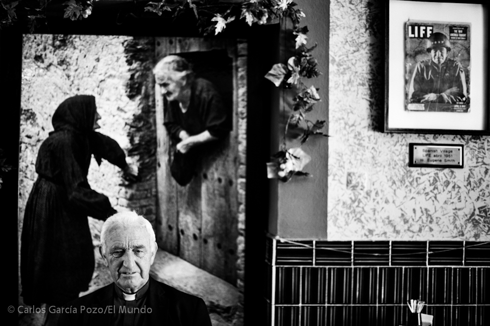 """El antiguo párroco, don Domingo, posa en el bar """" Spanish Village"""" frente a una reproducción de una imagen del ensayo de Eugene Smith y un ejemplar original de la revista Life donde se publicó."""