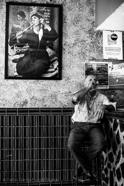 Un vecino se refresca con un botellín de cerveza en el bar bajo la mítica imagen de la hilandera de Smith.