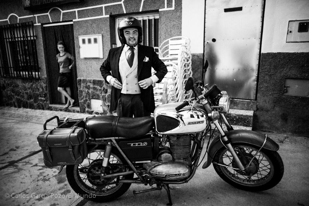 Pedro, el novio, se ajusta el chaqué antes de montar en su moto para ir a su boda.