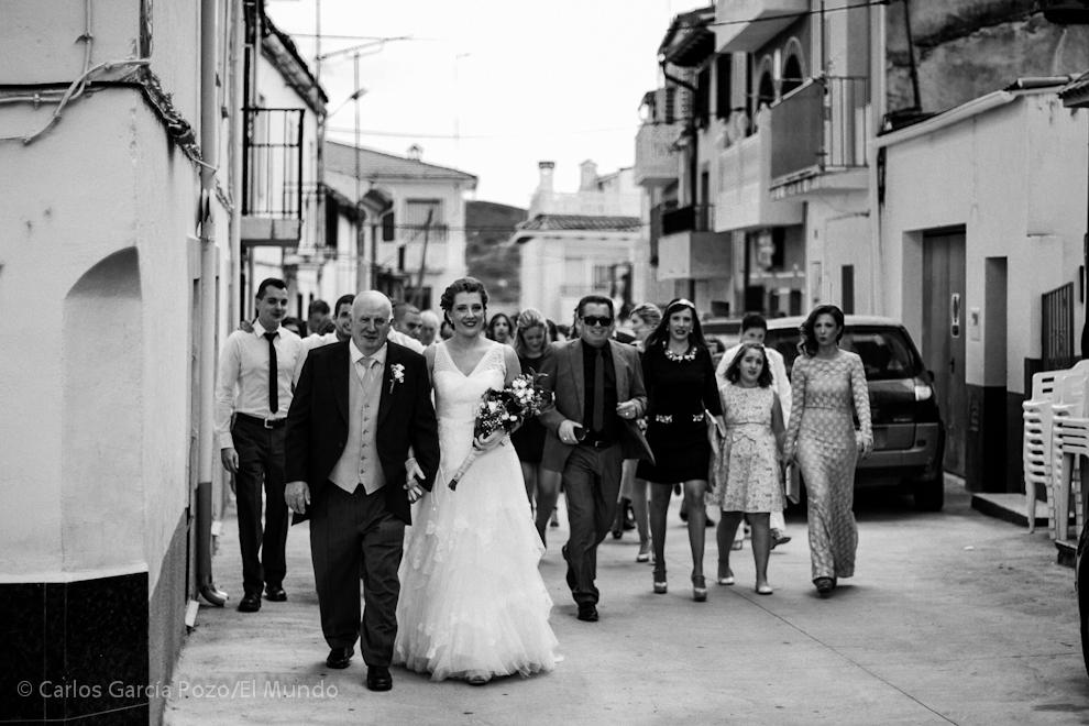 Sara,  la novia, del brazo del padrino sale de su casa dirección a la ceremonia.