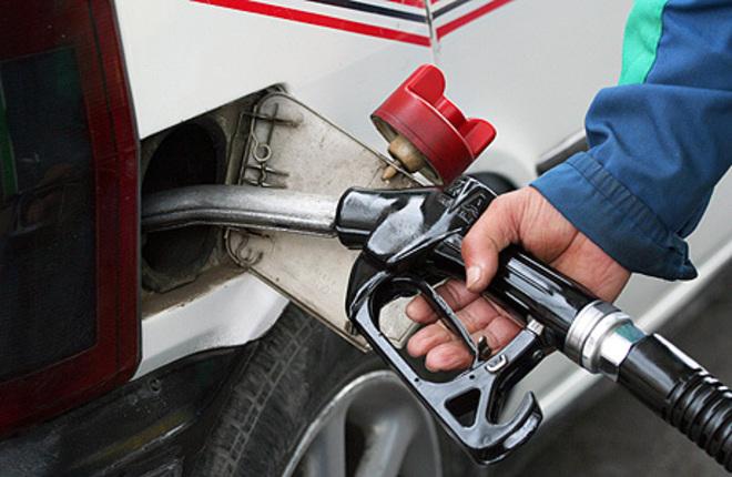 Un conductor reposta carburante en una gasolinera