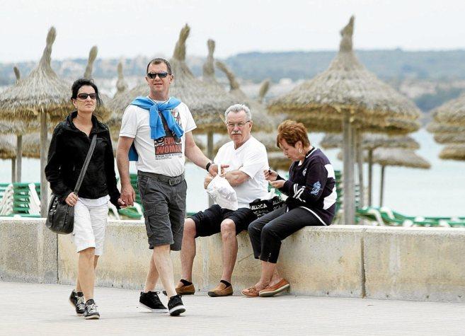 Turistas de la tercera edad descansando tras un paseo por una playa de...