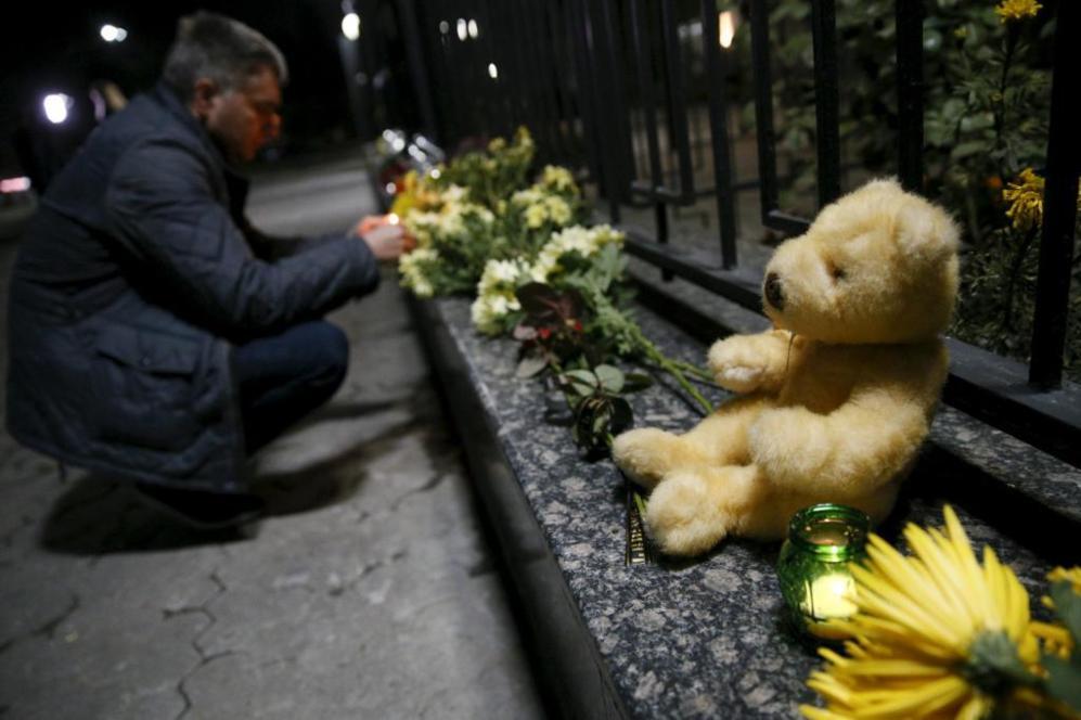 Un hombre enciende una vela junto a la embajada rusa de Kiev en...