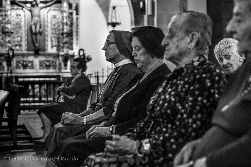 Cuatro vecinas y una religiosa rezan  el rosario en la iglesia del pueblo.