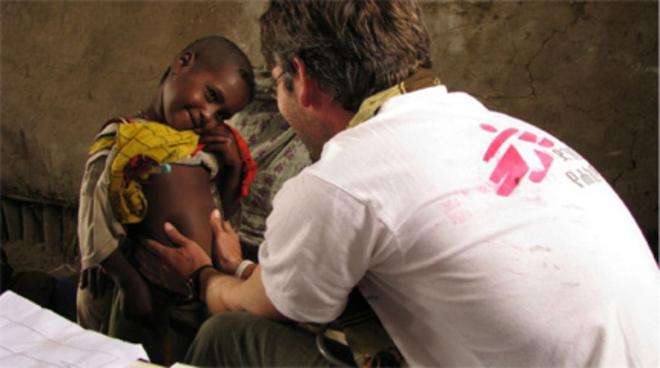 Un voluntario de Médicos Sin Fronteras atiende a un niño