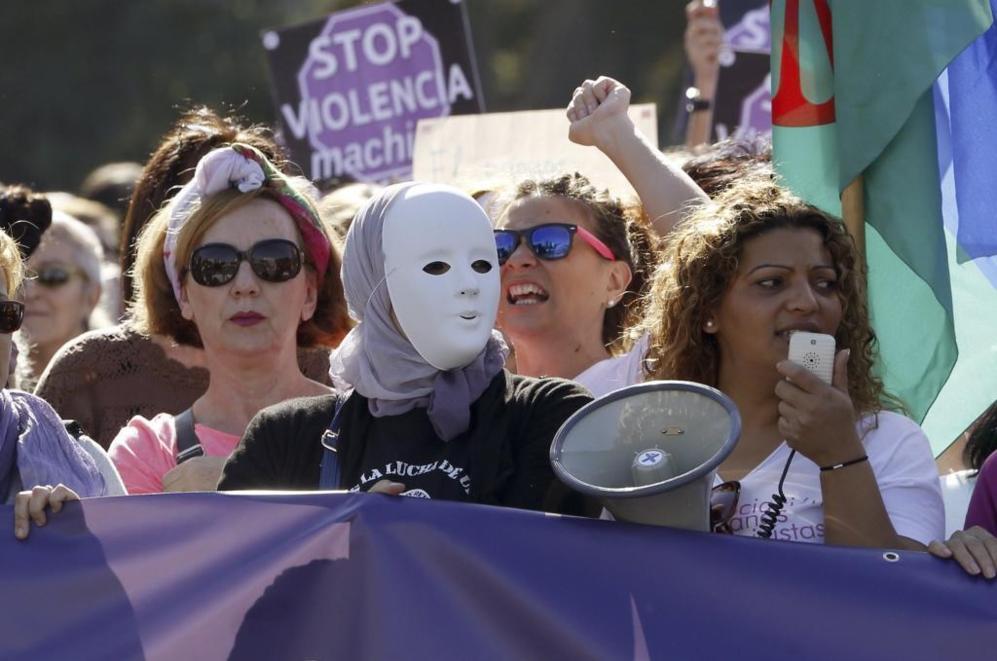 Una mujer con una careta y otra con el megáfono animando a los...