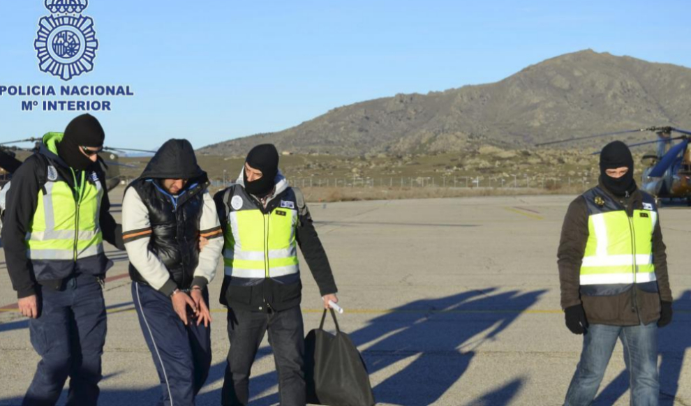 Policías nacionales llevan a un presunto yihadista detenido en Ceuta.