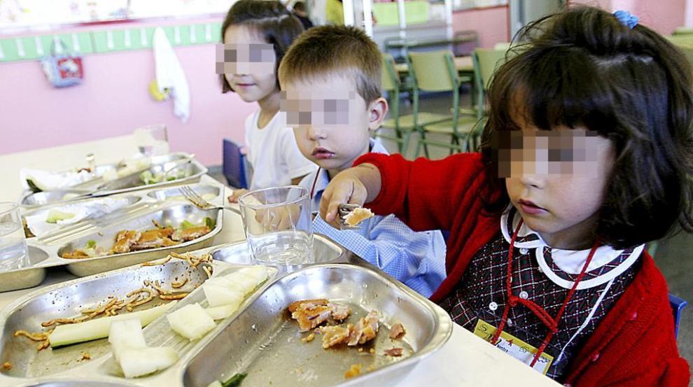 Varios niños comiendo en un colegio.