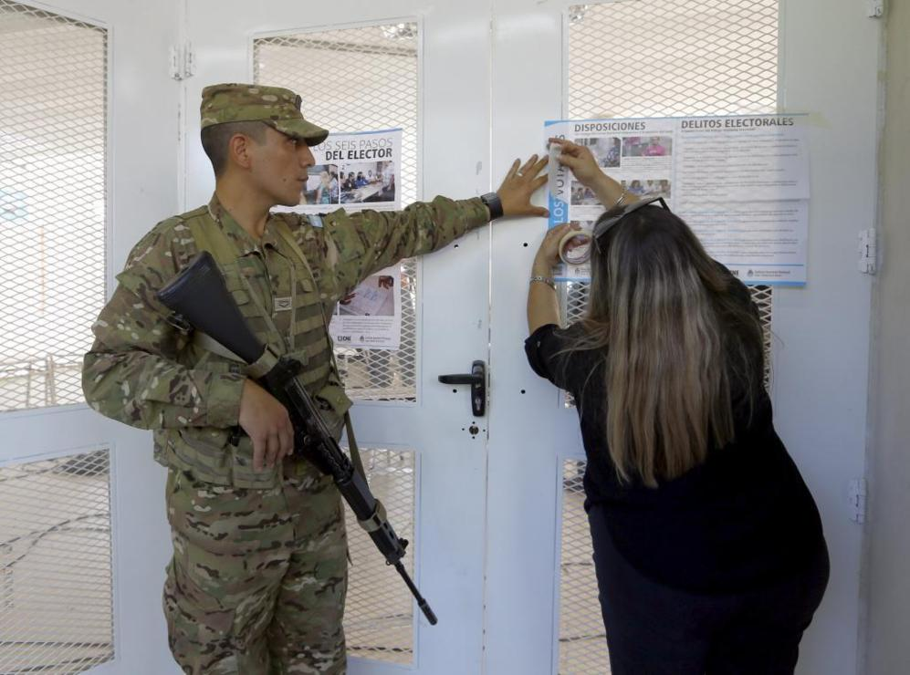 Un soldado ayuda a una mujer a colocar las disposiciones electorales.