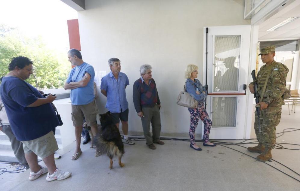 Un grupo de ciudadanos espera en la cola para entrar a votar.