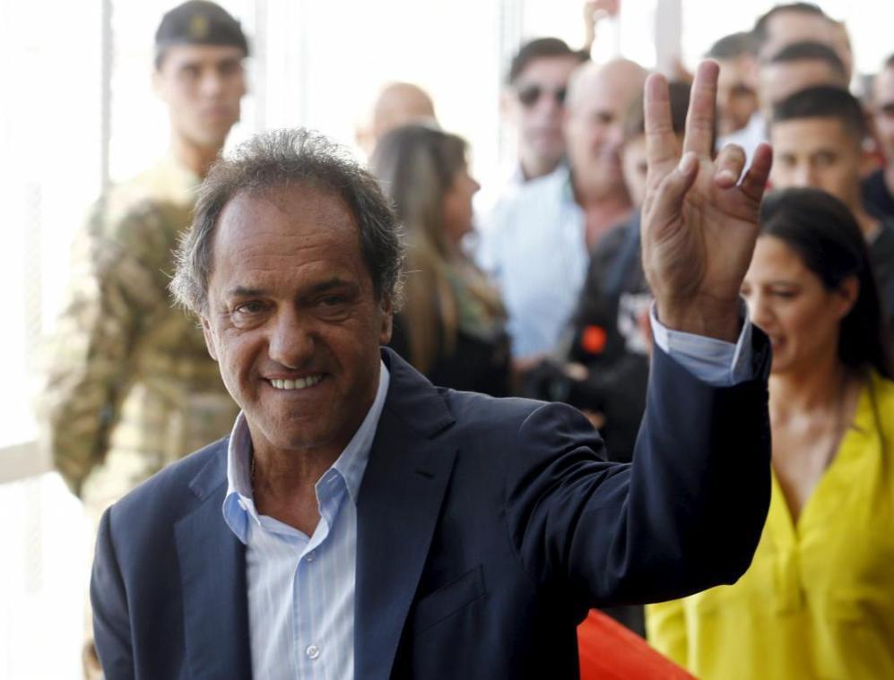 El candidato Daniel Scioli haciendo el símbolo de victoria a su...