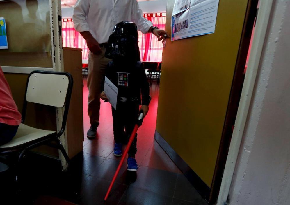 Un niño, disfrazado de Darth Vader, acompaña a su padre a votar en...
