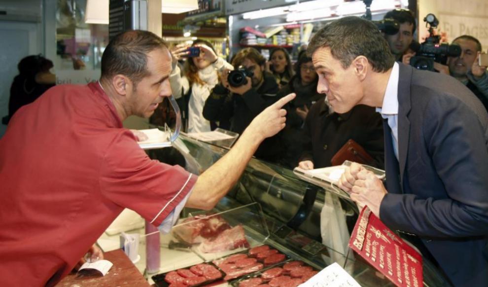 Pedro Sánchez habla con un carnicero del mercado de la Guineueta, en...