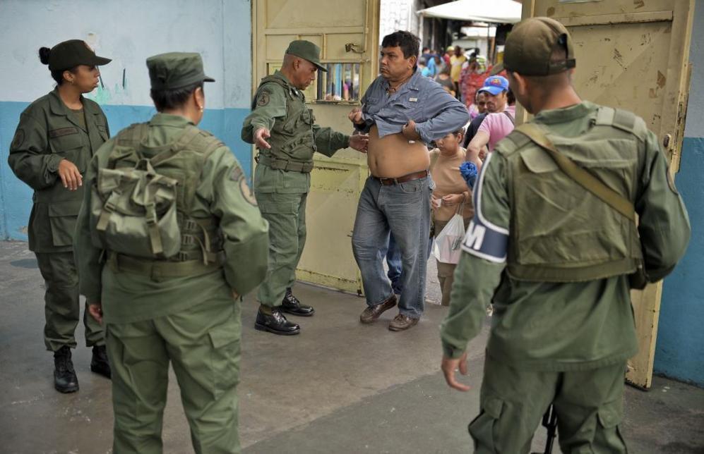 Los soldados inspeccionan a los votantes en busca de armas en Caracas.