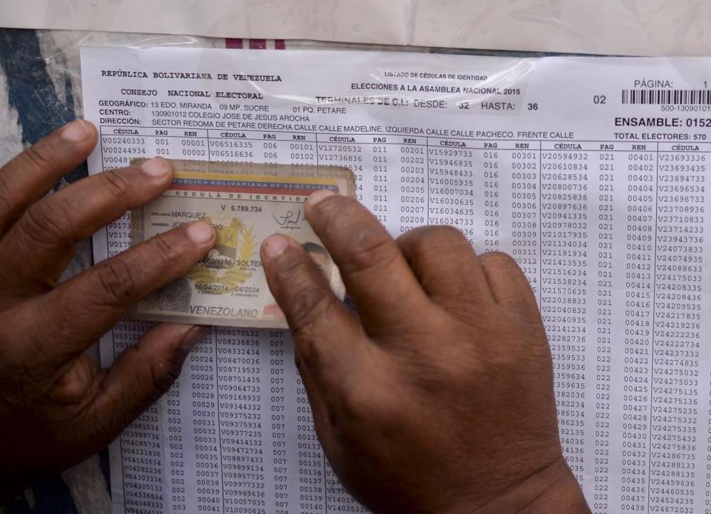 Un hombre busca el número de su cédula de identidad en un listado...