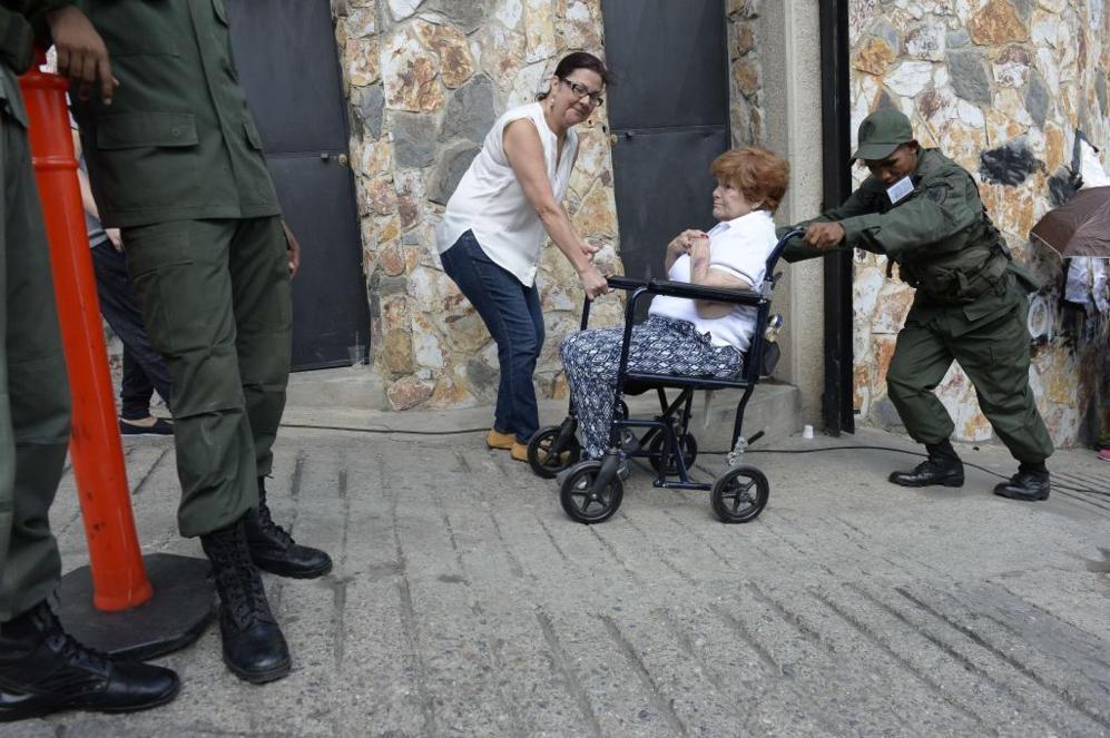 Los militares ayudan a que las personas con dificultades, como esta...