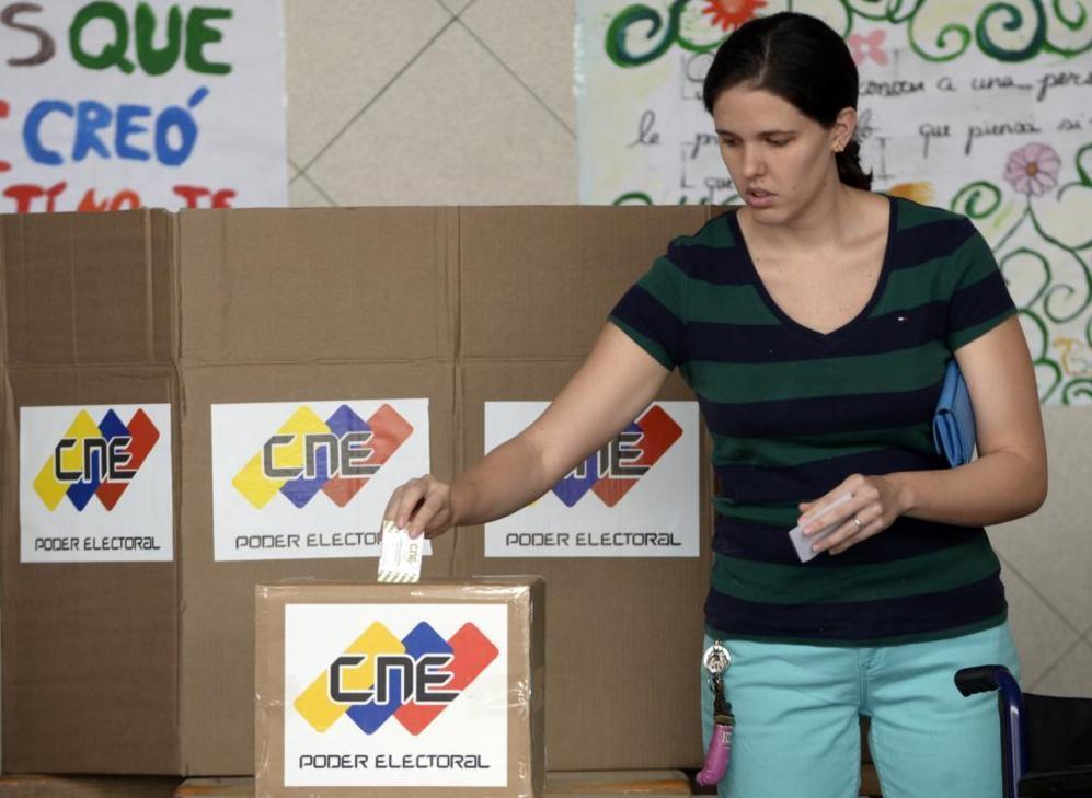 Una mujer deposita su papeleta en una urna de Caracas.