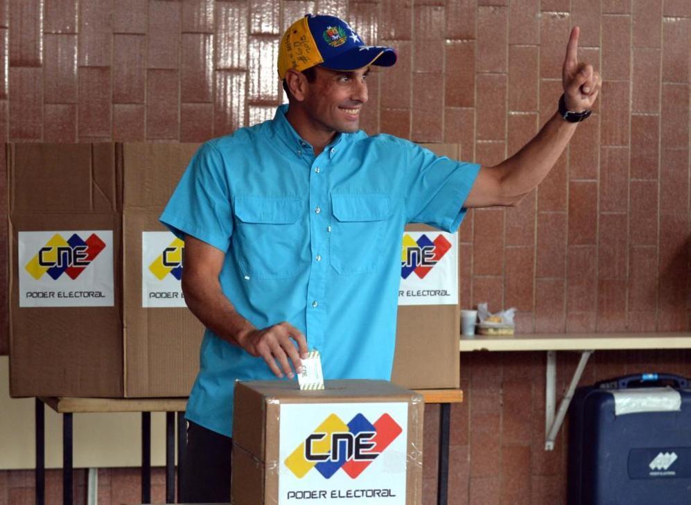 El opositor Henrique Capriles levanta un dedo mientras vota en...